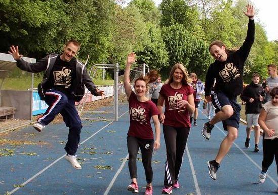 Schüler springen auf der Laufstrecke in die Höhe