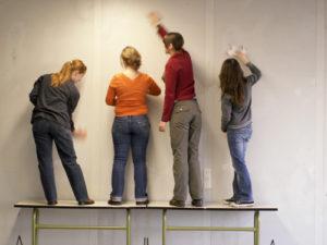 Vier Schüler streichen eine Wand