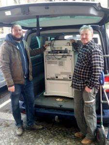 Zwei Männer mit Drucker im Kofferraum