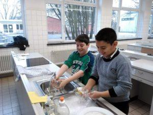 Zwei Schüler waschen ab.