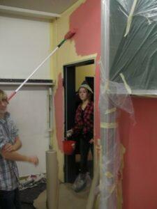 Schüler streicht Wand rot