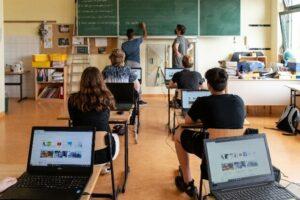 Schüler*innen mit Laptops im Klassenzimmer