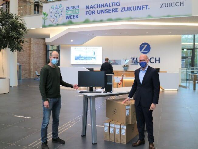 Zwei Personen posieren mit der PC Spende vor einem Tisch