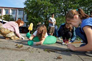 Schüler auf dem Schulhof mit Schaufel