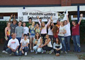 """Gruppenfoto mit Banner """"Wir verschönern unsere Schule"""""""