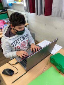 Junge, der am Laptop sitzt und tippt
